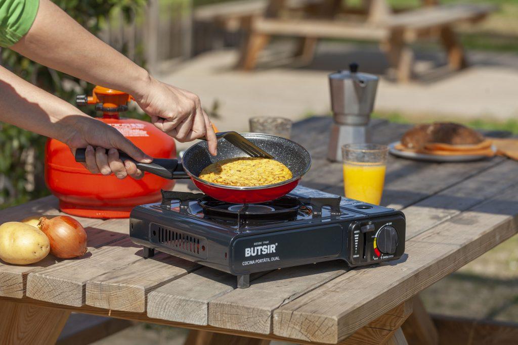 Plano de manos haciendo una tortilla en el exterior de un camping con la cocina portátil a gas DUAL de BUTSIR.