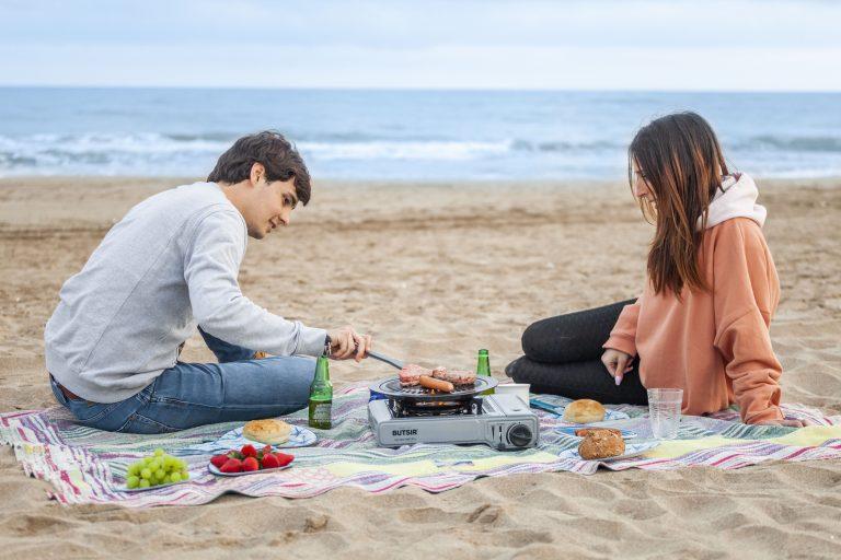 Pareja de picnic en la playa cocinando con la cocina portátil a gas BUTSIR MS-1000 PRO